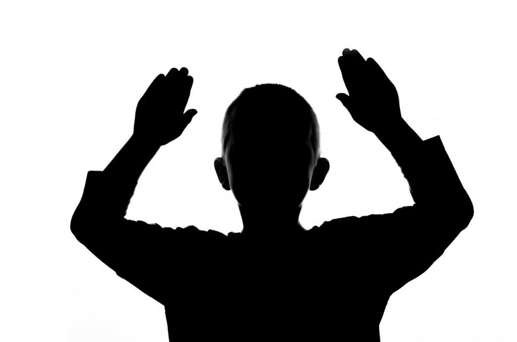 Silhouette of top half of a boy with hands in the air