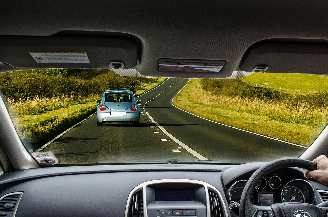 view out the windscreen of a car with 2 cars ahead on the road and grass either side of the road