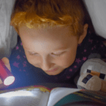 Boy reading by torchlight under his bed covers